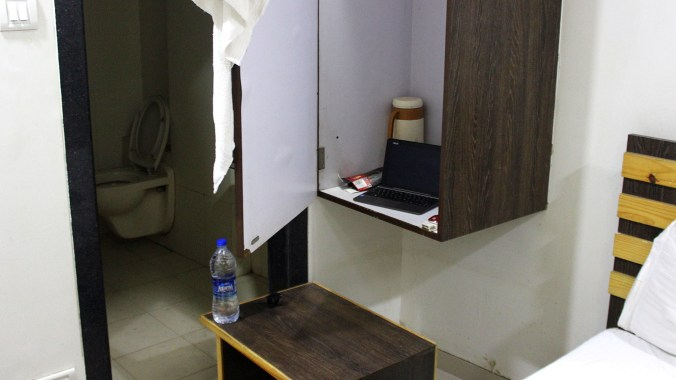 An improvised desk with laptop on a locker and hotel room nightstand used as a chair.
