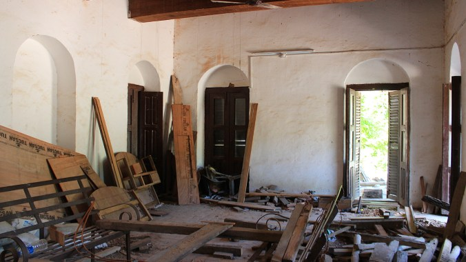 A construction site inside the Ranighat Palace, with plenty of wooden boards spread around.
