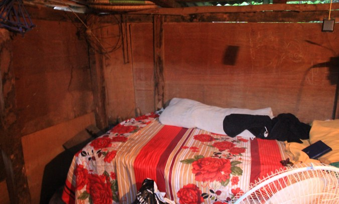 A room in a Nepalese shack with a small bed and walls made of chipboard.
