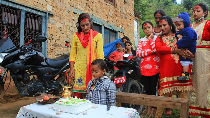 A Nepalese boy celebrating birthday with relatives and a cake.