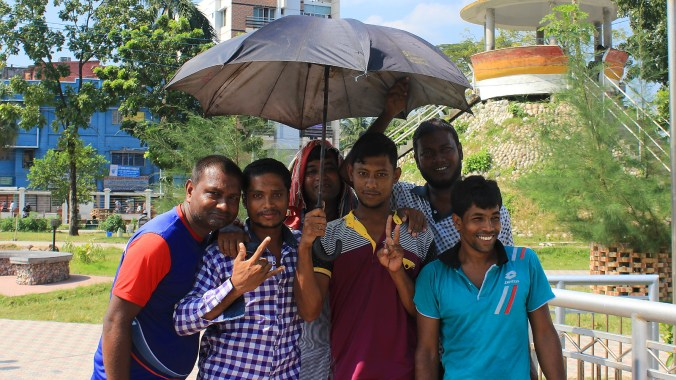 People of Bangladesh. A group of young men posing for the camera under an umbrella.