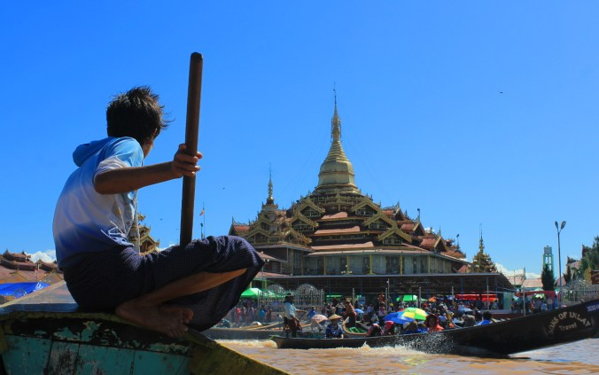 Pictures of Myanmar. A young boy leading a boat to Hpaung Daw U Pagoda in Inle Lake.