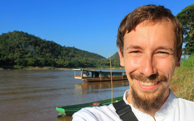 Arimo Koo travels. RTW travel blogger taking a selfie by Luang Prabang dock with a slowboat in the background.
