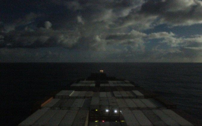 Traveling on a cargo ship across the Pacific Ocean during the night.