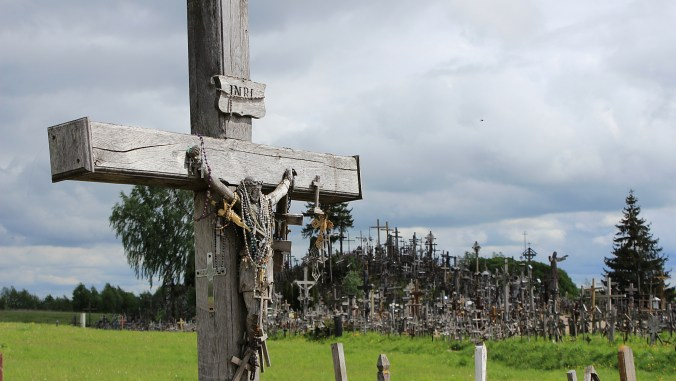 A wooden crucifix with the Hill of Crosses in the background.