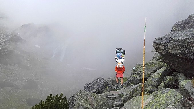 A man carrying food and supplies on a mountain path to the Tery Cabin in High Tatras.