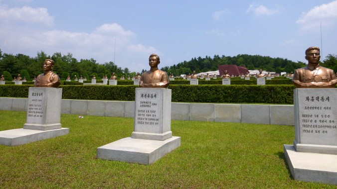 Revolutionary Martyrs' Cemetery in North Korea with bronze busts on graves.