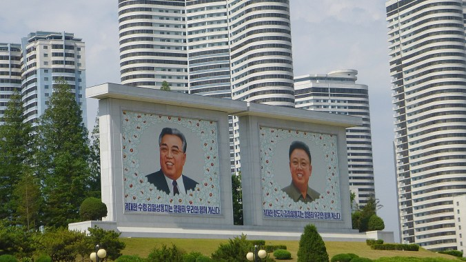 Billboards of Kim Il-Sung and Kim Jong-Il with flowers in a park in Pyongyang.