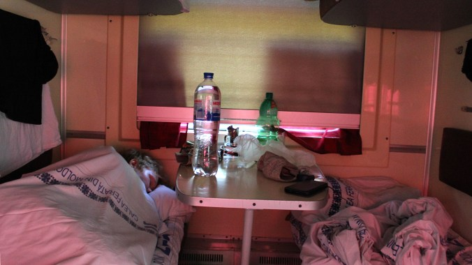 A tourist sleeping on the lower berth of a sleeper car of a train in Eastern Euroe.