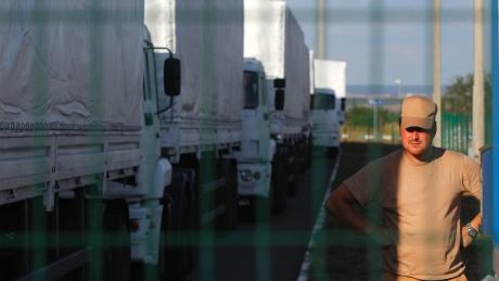 White trucks and a man photo shot through a fence