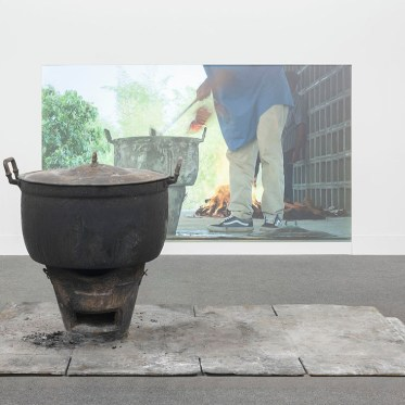 "RIRKRIT TIRAVANIJA, ""Untitled 2014 (curry for the soul of the forgotten)"" 43 min video projection, bronze fire pot, Size Variable, 2014. Image © Tang Contemporary Art"