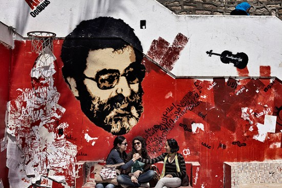 Shams (L), who won the Student Union elections at her university in Tunis, sits with her colleagues at her favorite spot, which is graffitied with an image of assassinated Lebanese thinker Mahdi Amel. Shams, a street poet and activist, said that Amel's slogans were painted over in white by some conservative students.