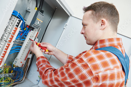 Electrician works with screwdriver in fuse box - Buy this stock