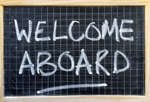 The words Welcome Aboard written by hand on a blackboard as an - welcoming messages for new employees