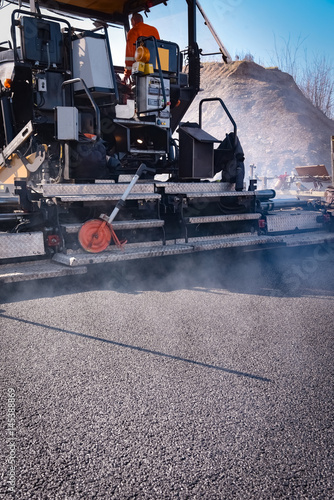 asphalting a new road with a tar machine, high format - Buy this