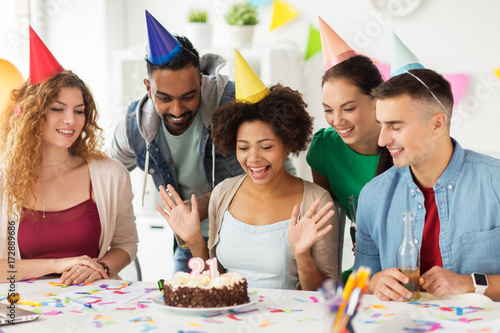 team greeting colleague at office birthday party - Buy this stock