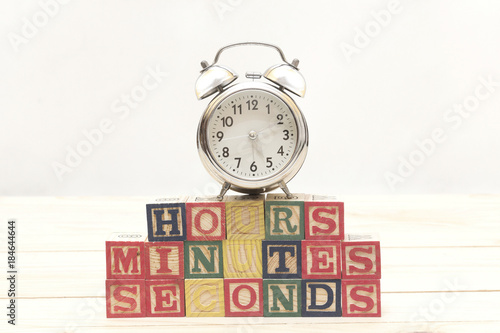 Clock with wood cubes on wooden table words hours,minutes,seconds