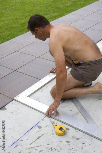 tile-layer who poses tiling on a terrace - Buy this stock photo and