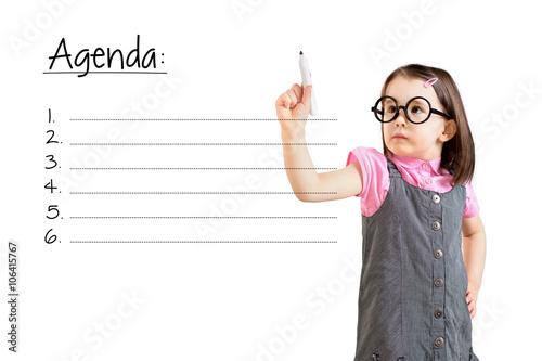 Cute little girl wearing business dress and writing blank agenda