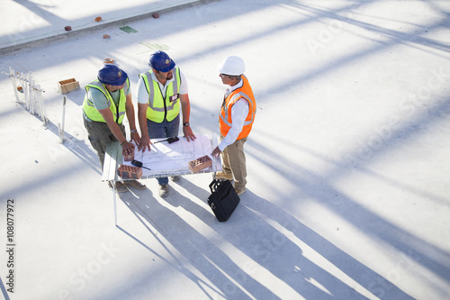 Architects reading blueprints at construction site - Buy this stock