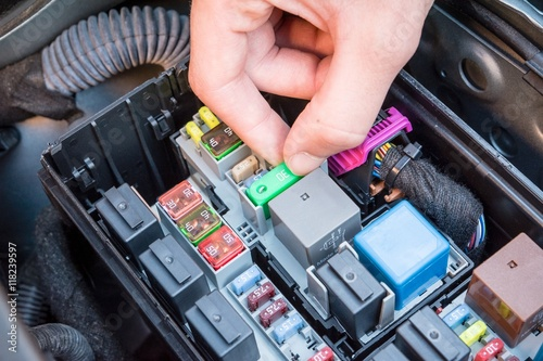 Hand checking a fuse in the fuse box of a modern car engine - Buy
