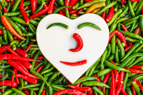 White heart shaped on red and green chili peppers, Concept of hot