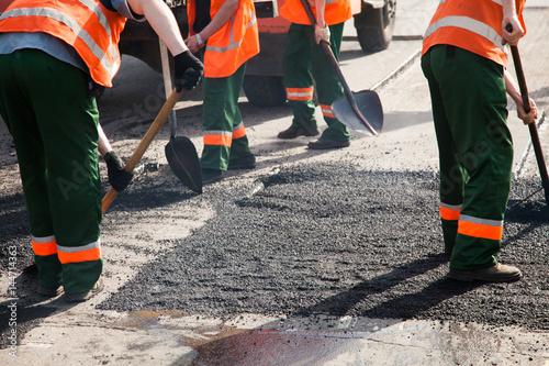 Workers on Asphalting paver machine during Road street repairing