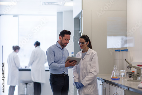 Female scientist discussing data with pharmaceutical sales rep - Buy