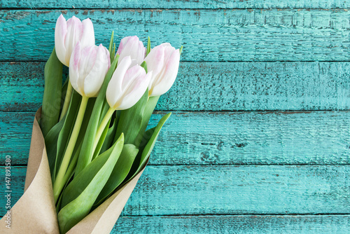 light pink tulips bouquet on turquoise wooden tabletop with copy