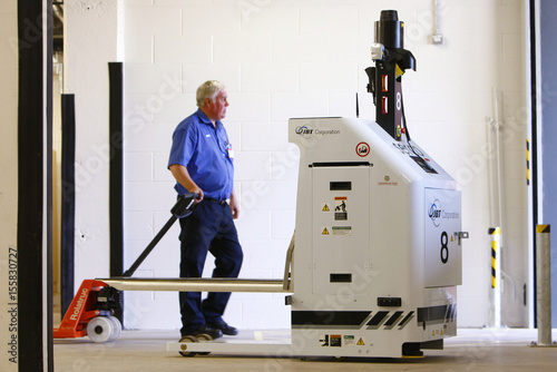 A hospital porter walks past one of the new robots currently being