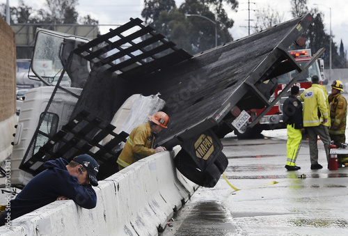 The driver of a bobtail truck hangs his head as firefighters try to