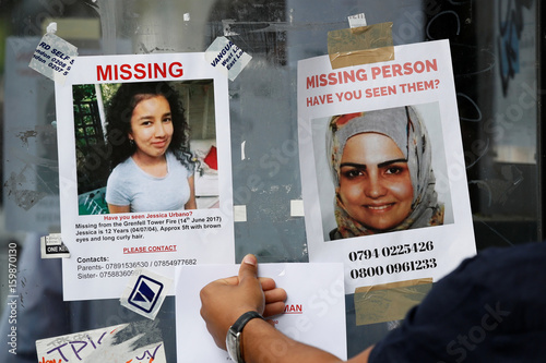 A woman touches missing person posters near The Grenfell Tower block