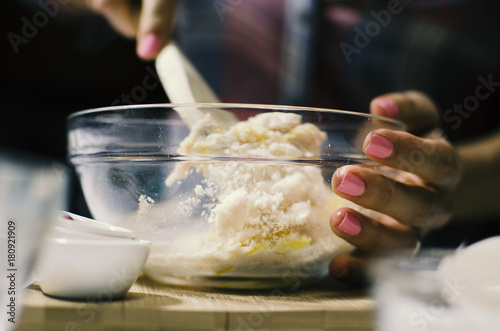 Woman in kitchen mixing dough in bowl for food prep Cooking shown