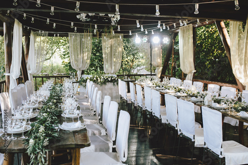 Decorated elegant wooden wedding table for banquet outdoor in garden