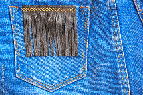 Fragment of jeans trousers with a pocket decorated with leather