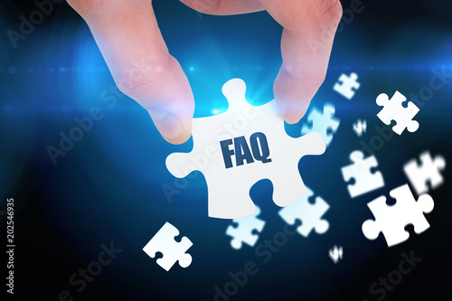 The word faq and hand holding jigsaw piece against blue background
