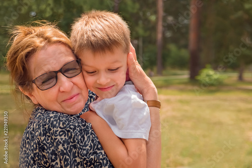 Family background Grandmother with her grandson embracing firmly