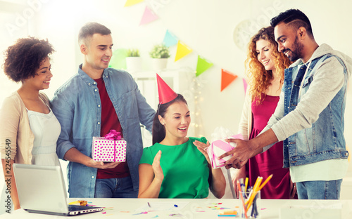 corporate, celebration and people concept - happy team with gifts