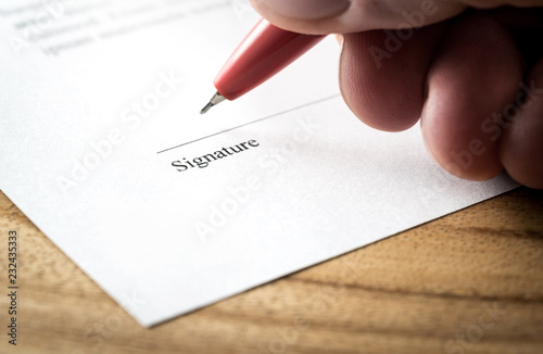 Writing signature Man signing settlement, contract or agreement for
