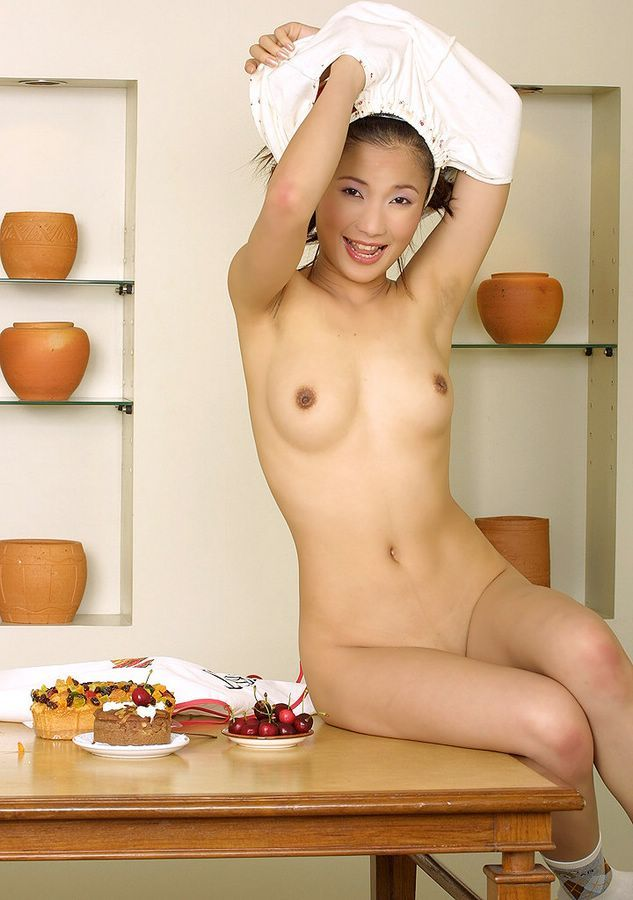 Asian girl squeezes her huge boobs in a photo studio