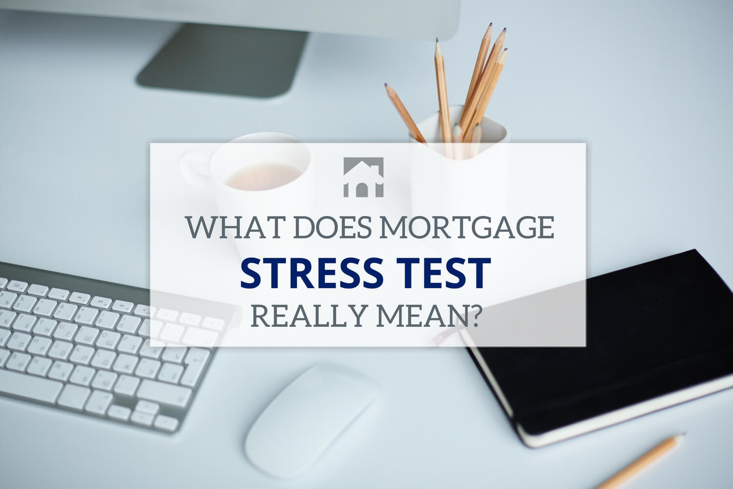 Image of a desktop with phone, plant, keyboard on mouse with text overlay that reads What Does Mortgage Stress Test mean
