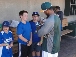 Chris Young autographs balls for some inappropriately-attired youngsters in the A's dugout before the game