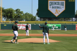 Stephen Vogt lends Ron Washington a helping hand during batting practice