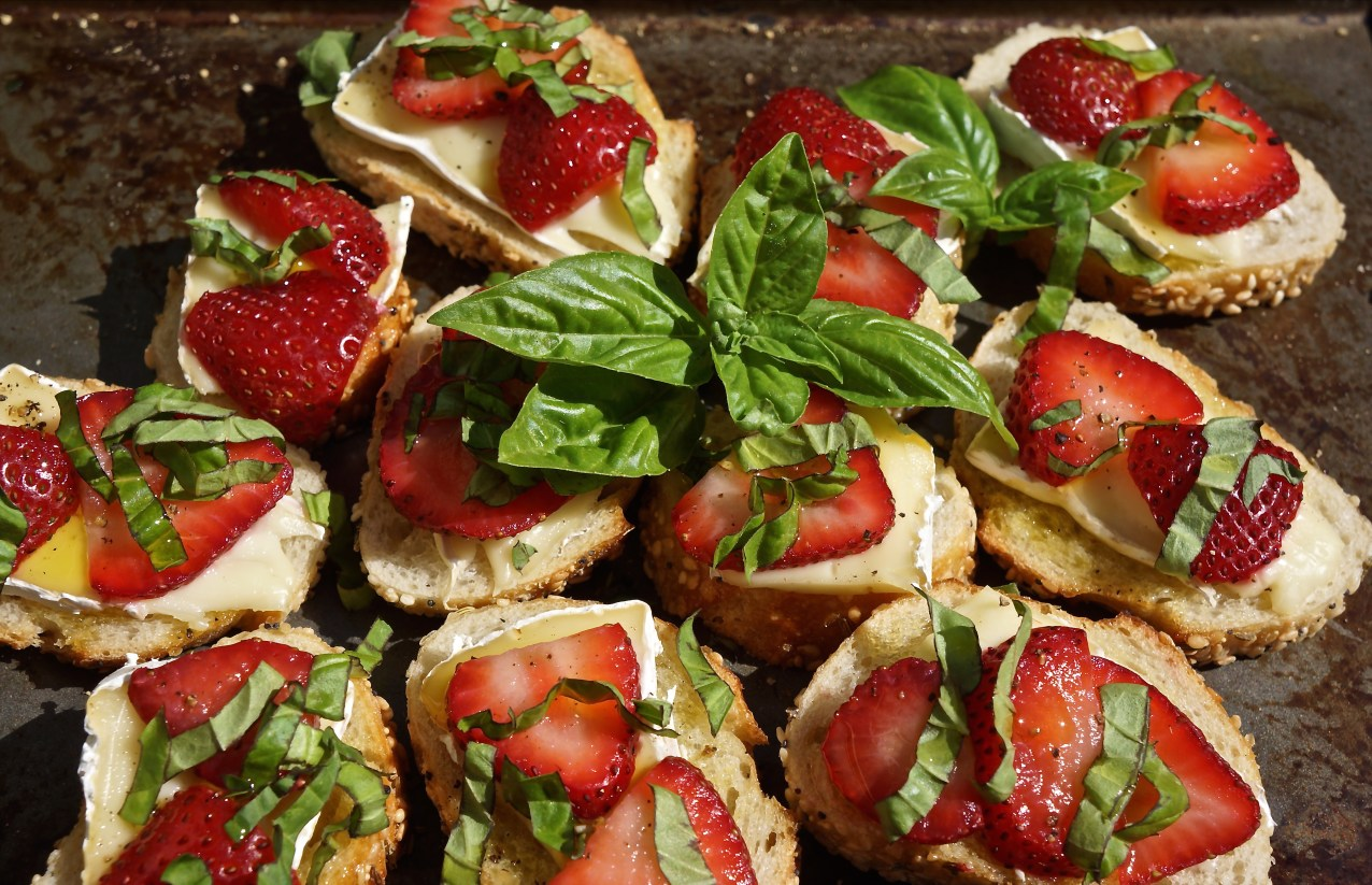 Placing the toasted side down, top each crostino with brie cheese and sliced strawberries. Top each with freshly ground black pepper, fresh basil and drizzle of olive oil.
