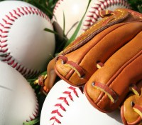 A baseball glove surrounded by balls on a field