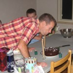 "Dad blowing out the candles on his  ""Killer Chocolate Cake"""