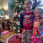 Kids posing in front of the Christmas tree.