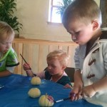 The kids painting pumpkins.