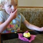 Eating her cupcake.