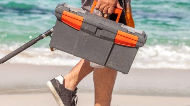 Man walking on the beach holding in one hand a tackle box and a fishing rod in the other.